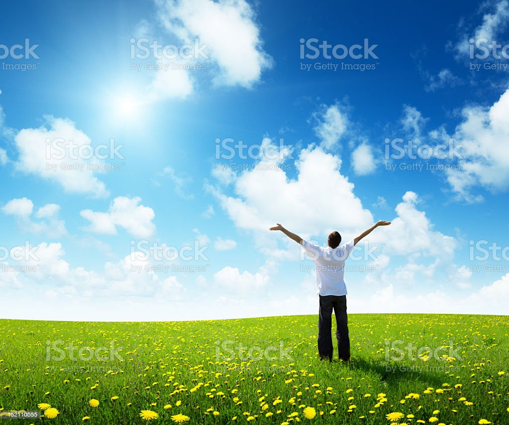 Man with outstretched arms standing in a sunny green field royalty-free stock photo