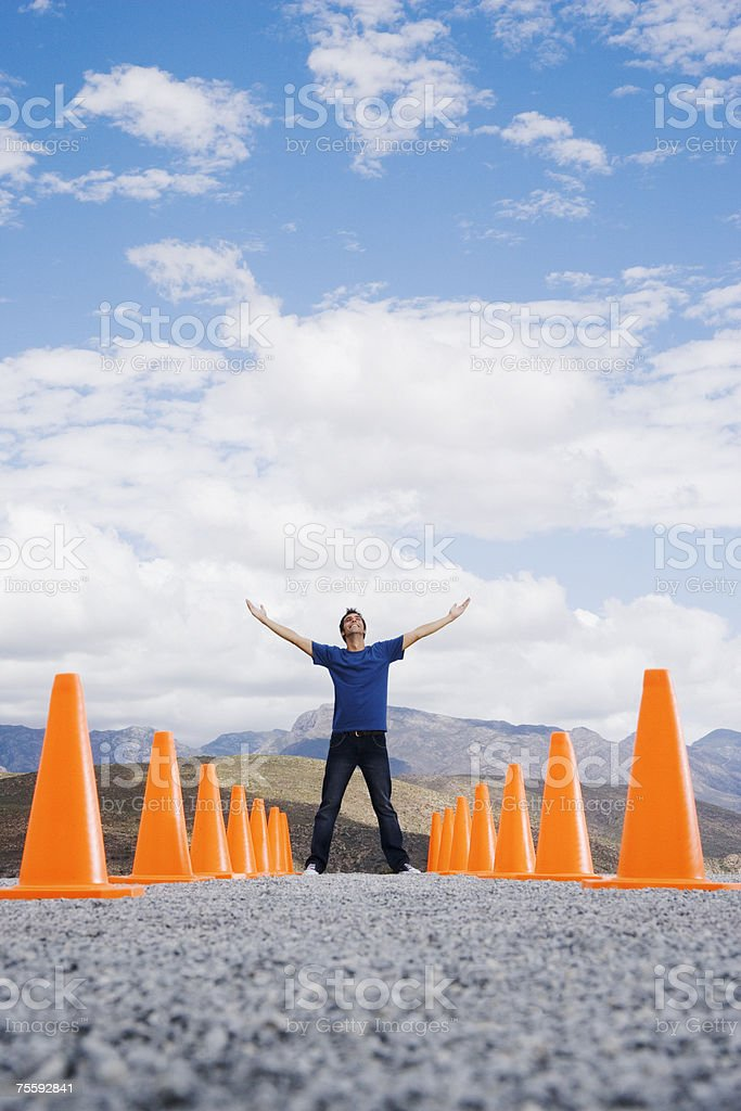 Man with outstretched arms standing in-between two rows of safety cones royalty-free stock photo