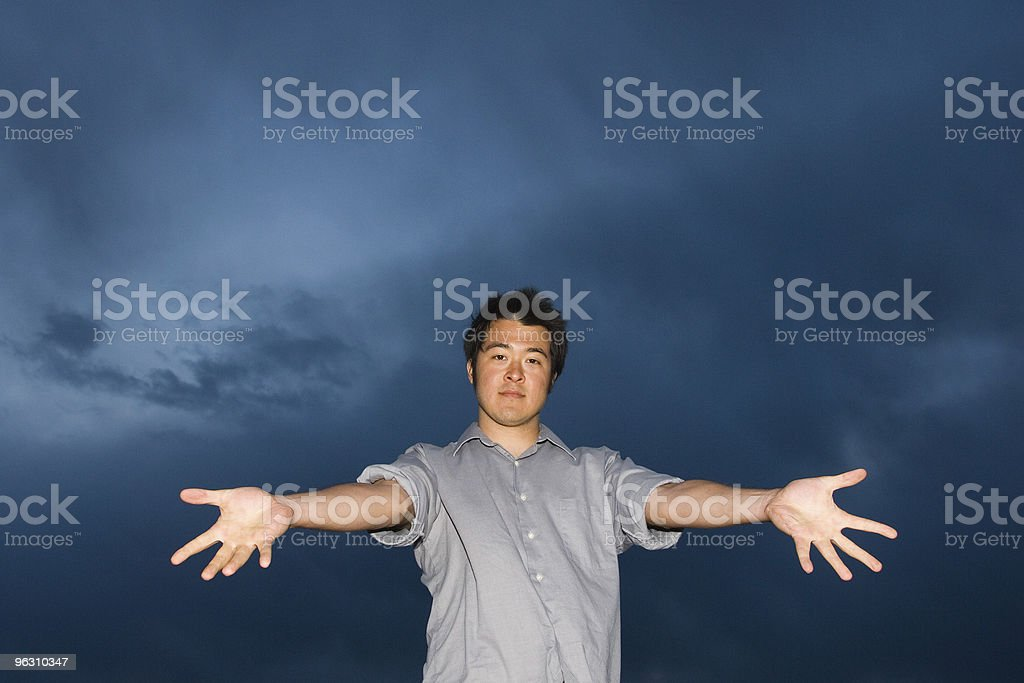 Man with outstretched hands aganst stormy sky royalty-free stock photo