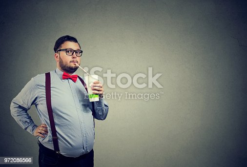 1067846662 istock photo Man with overweight drinking sweet soda 972086566