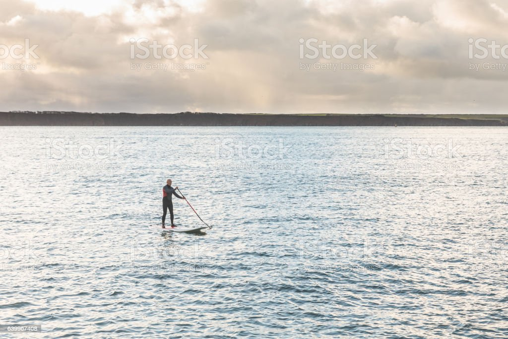 Man with paddle board over the cliffs stock photo