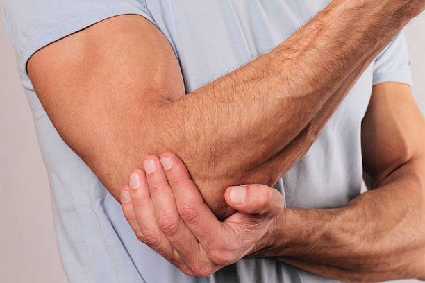 Man With Pain In Elbow. Pain relief concept stock photo