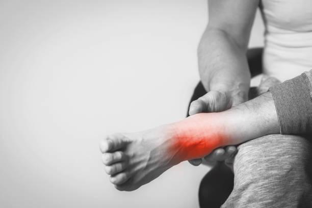 man with pain in foot - caviglia foto e immagini stock
