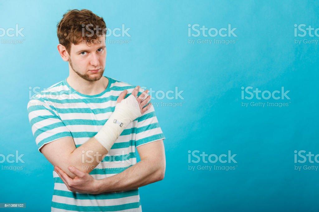 Man with painful bandaged hand. stock photo