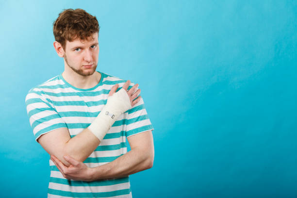 Man with painful bandaged hand. stock photo