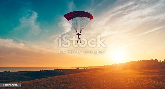 Sun shines and is about to set in the horizon as man parachutes through the air. He is about to land on the ground.  Note: The man and parachute is made in a 3D program. Property release attached.