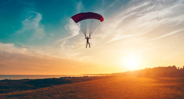 Man with parachute is about land on the ground while the sun shines Sun shines and is about to set in the horizon as man parachutes through the air. He is about to land on the ground.  Note: The man and parachute is made in a 3D program. Property release attached. parachuting stock pictures, royalty-free photos & images