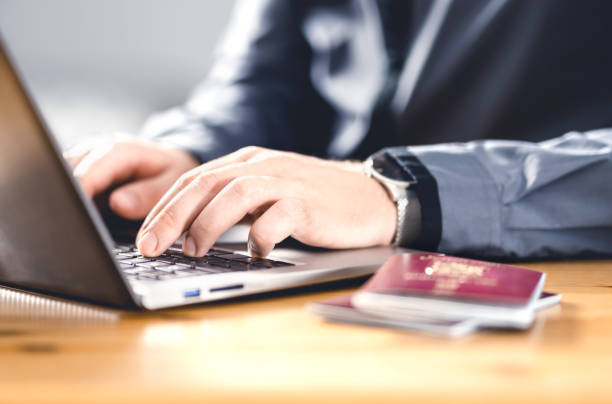 Man with passport and laptop. Travel document and identification. Immigrant writing electronic application for citizenship. Apply for digital visa. stock photo