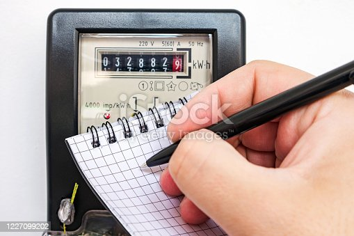 693910734 istock photo Man with pen and notepad writes the electrical meter readings. Payment of utility services. 1227099202