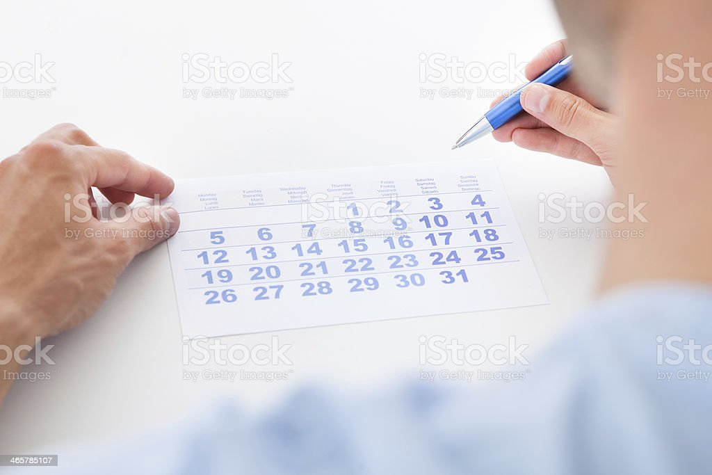 Man With Pen Looking At Calendar royalty-free stock photo