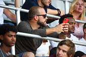 Man holding his red smart phone sitting on stadium among crowd.