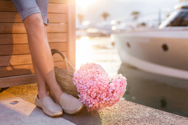 Man with pink flower heart waits woman on romantic date in traveling at sunset near yachts. Tourist prepares gift and surprise sailing on valentine's day in honeymoon vacation. stock photo