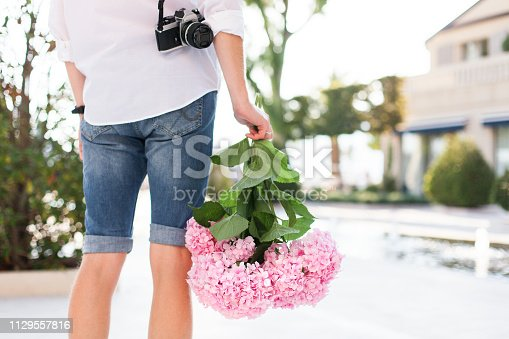 Man with pink flower hydrangea and film photo camera is waiting woman on romantic date in traveling at sunset in city park. Boy is wearing in casual denim shorts and white shirt outdoor.