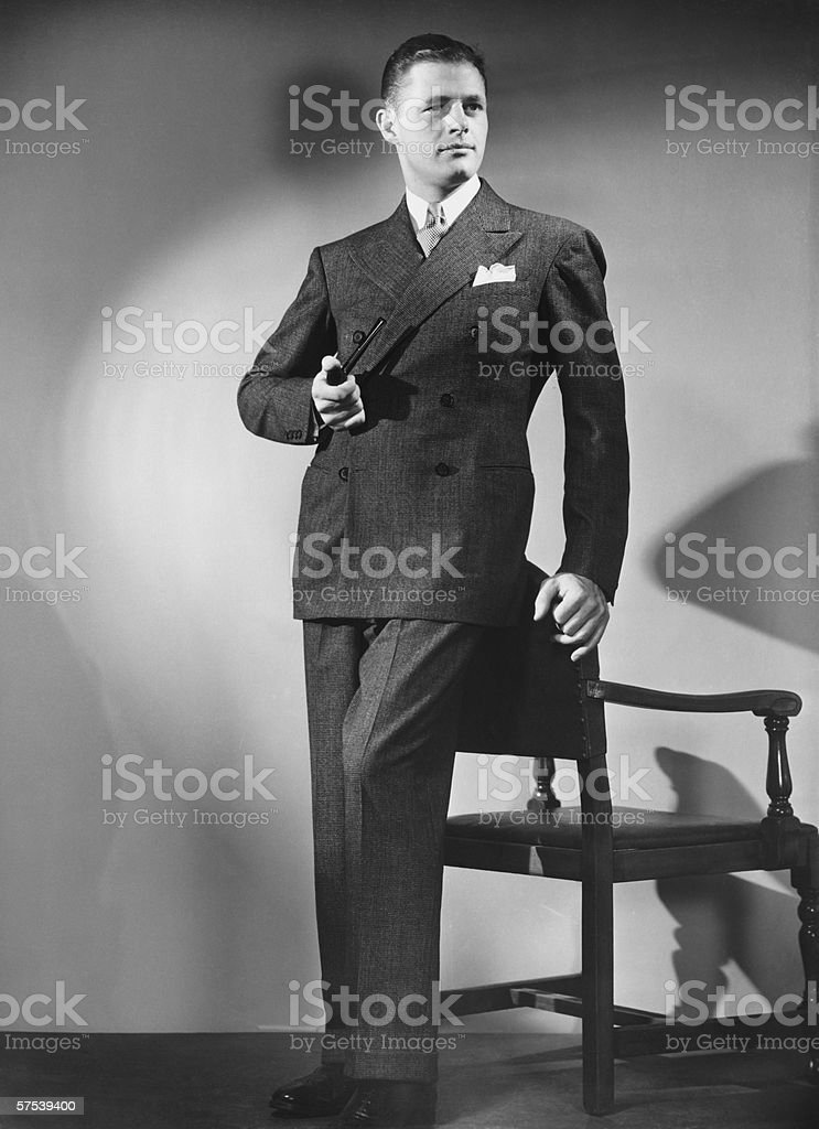 Man with pipe posing by chair in studio, (B&W), portrait stock photo
