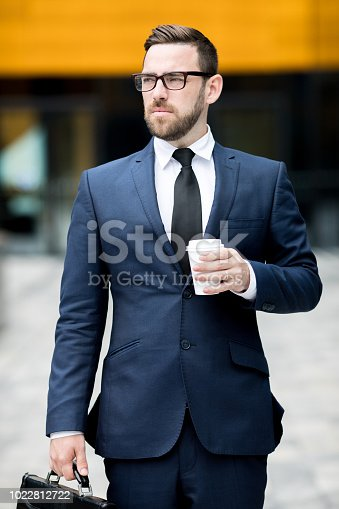 Young successful handsome male in business dress, eyeglasses holding cup with hot drink and looking away