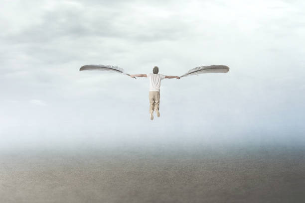 man with plumes wings fly in the sky stock photo