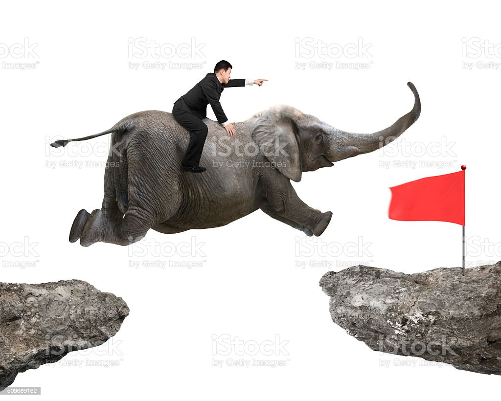 Man with pointing finger riding elephant flying toward red flag stock photo