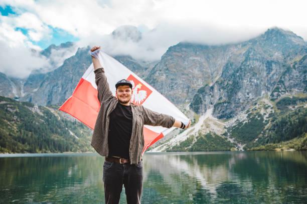 man with poland flag at eye of sea lake in tatra mountains stock photo