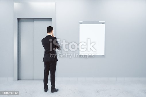 638591126istockphoto Man with poster and elevator 908286148