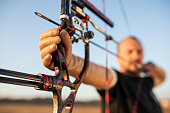Man with prosthetic arm practicing archery with compound bow on the field on training at sunset. Focus on archer's hand