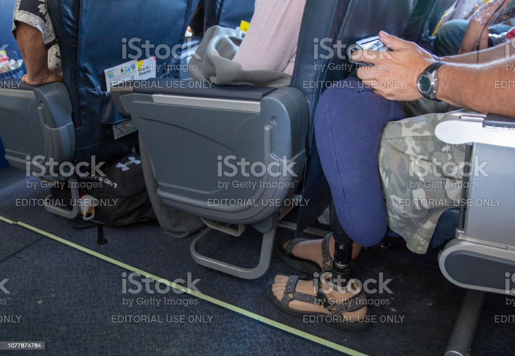 Man with prosthetic leg is cramped sitting in his seat on an airplane Fort Lauderdale,Florida, United States-July 12, 2018: An airplane is waiting to take off from the airport in Fort Lauderdale. A man is very cramped sitting in an aisle seat. He has a prosthetic leg. It is often uncomfortable for passengers sitting in economy. The seats are very close together. Shot with Canon 5D Mark lV. Adult Stock Photo