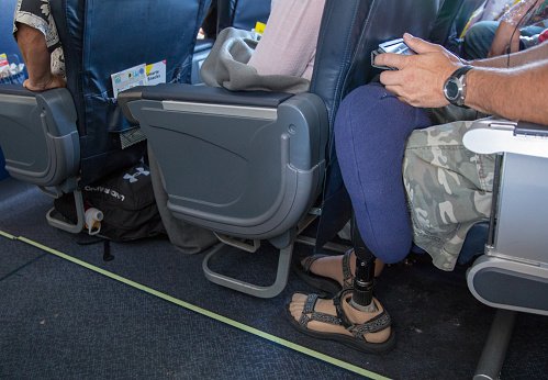 Man With Prosthetic Leg Is Cramped Sitting In His Seat On An Airplane Stock Photo - Download Image Now