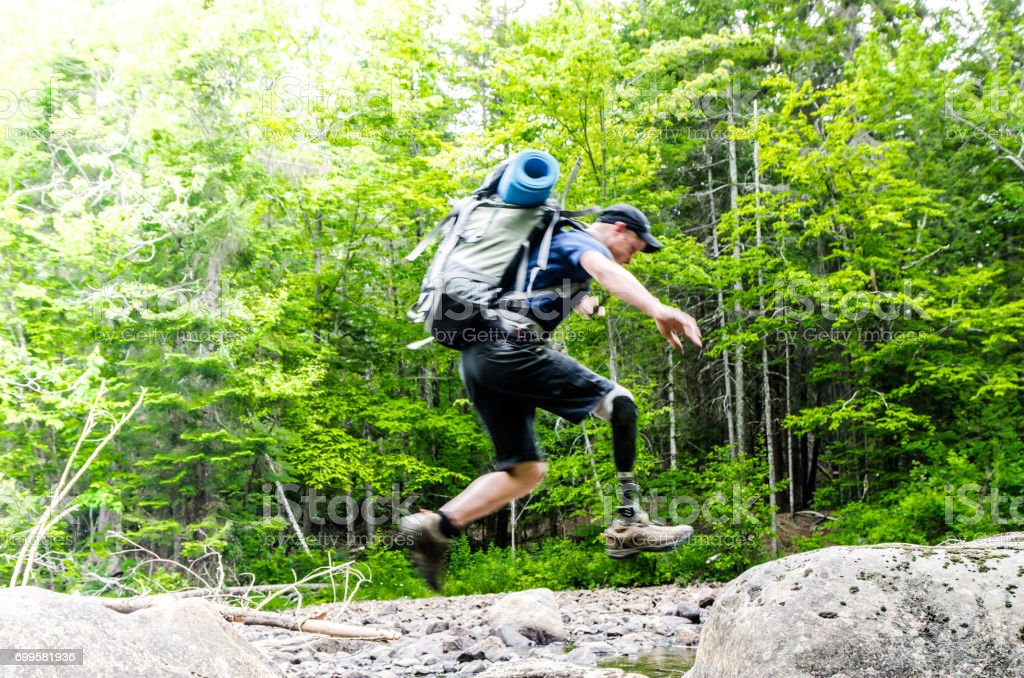 Man with prosthetic leg jumping on rocks to cross a river stock photo