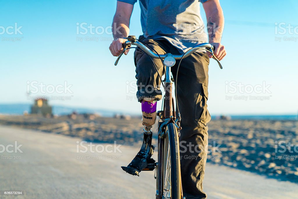 Man with prosthetic leg riding a bicycle stock photo