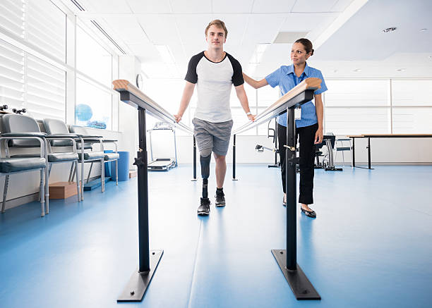 man with prosthetic leg using parallel bars with physyiotherapist - australian nurses stock photos and pictures