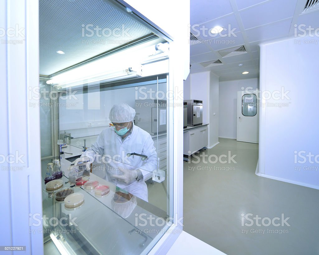 Man with protective coat and mask under fume hood stock photo
