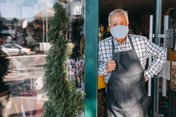Man with protective face mask at entrance of flower shop stock photo