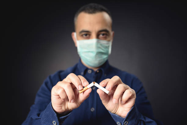 Man With Protective Face Mask Breaking Cigarette After COVID-19, Quit Smoking Concept stock photo