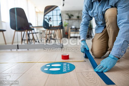 Unrecognizable man with protective gloves putting adhesive tape on six feet distance, in front of information sign about social distancing in front of bank counter