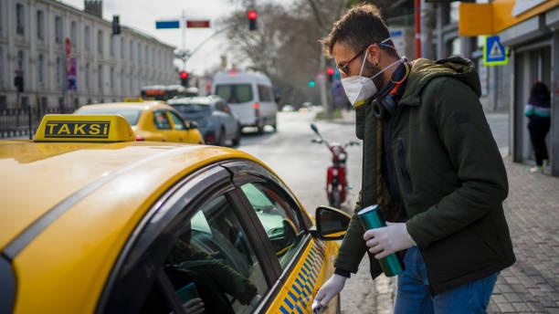 タクシーを取る保護マスクを持つ男 - corona newyork ストックフォトと画像