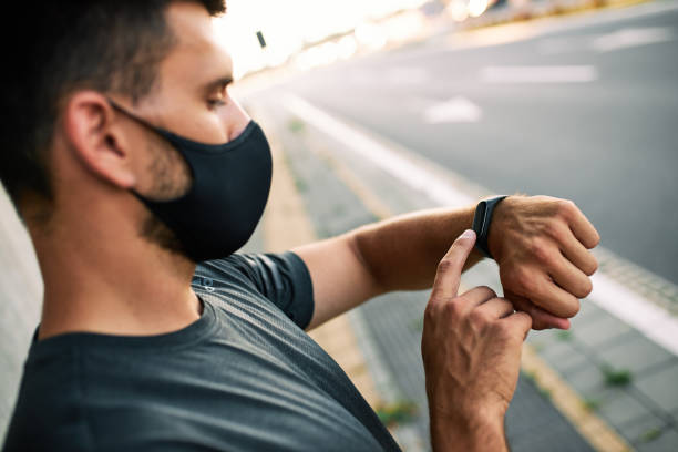 Man with protective mask using his smart watch stock photo