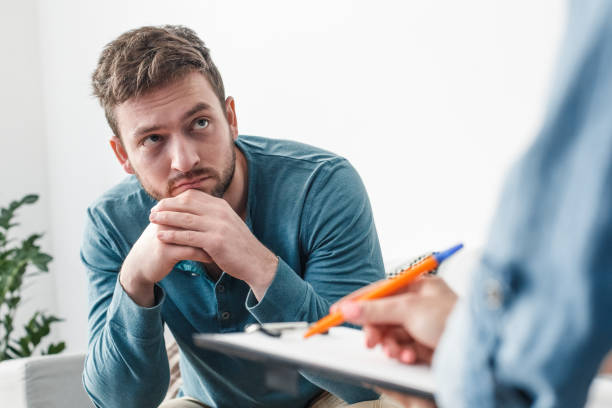 Man with psychologist theraphy social problems concept drug addiction Man with psychologist drug addiction problems concept sitting on sofa looking at doctor taking notes close-up dependency stock pictures, royalty-free photos & images