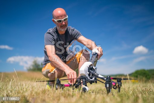 man preparing drone uav quadrocopter for takeoff inserting battery, shallow depth on battery