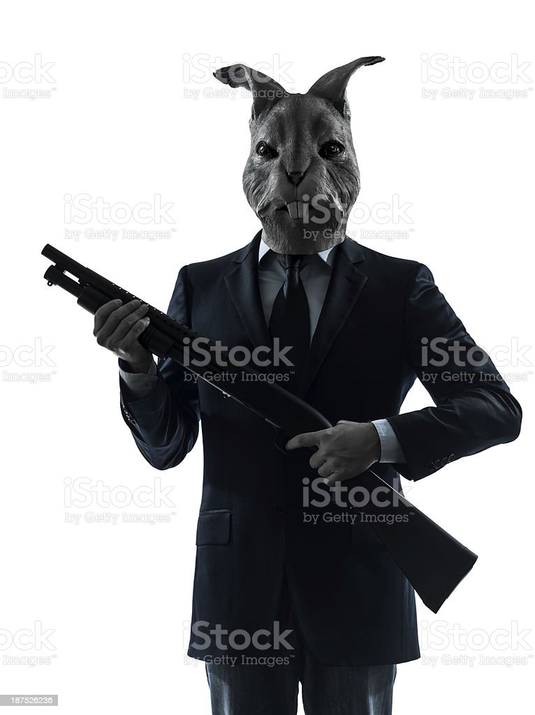 man with rabbit mask hunting shotgun silhouette portrait stock photo