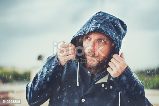 Man with raincoat under heavy rain