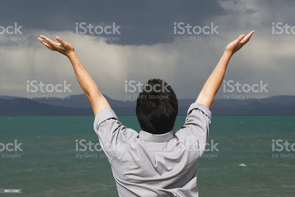 Man with raised hands aganst stormy sky royalty-free stock photo