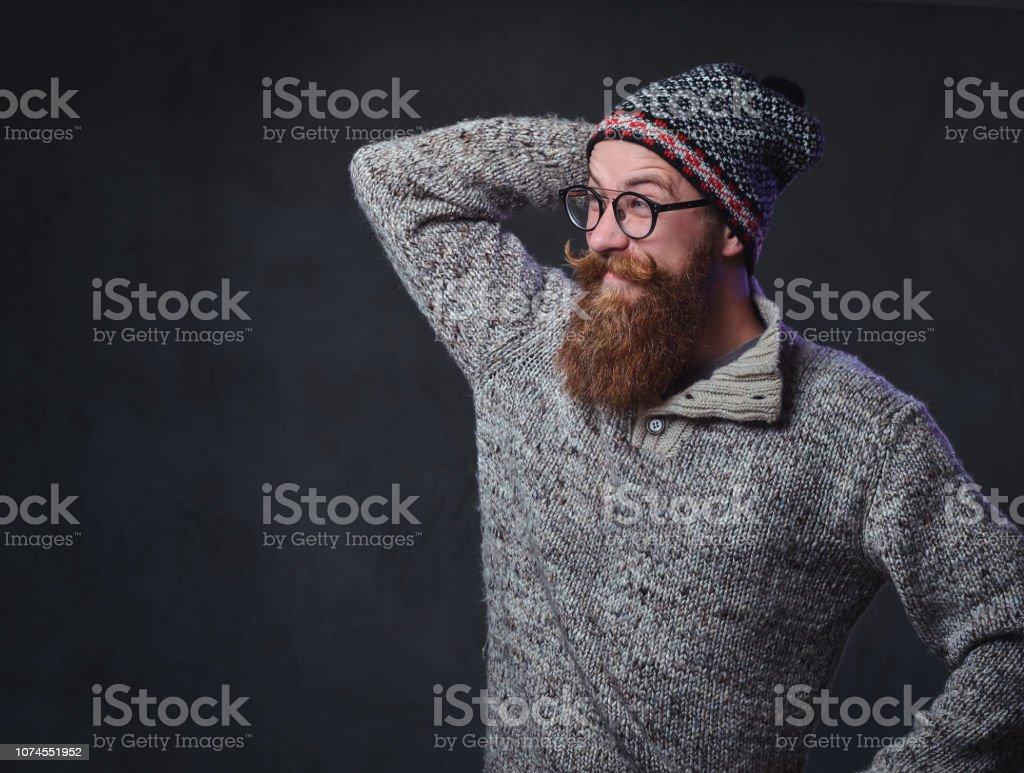 Portrait of a bearded redhead male in eyeglasses dressed in a wool...