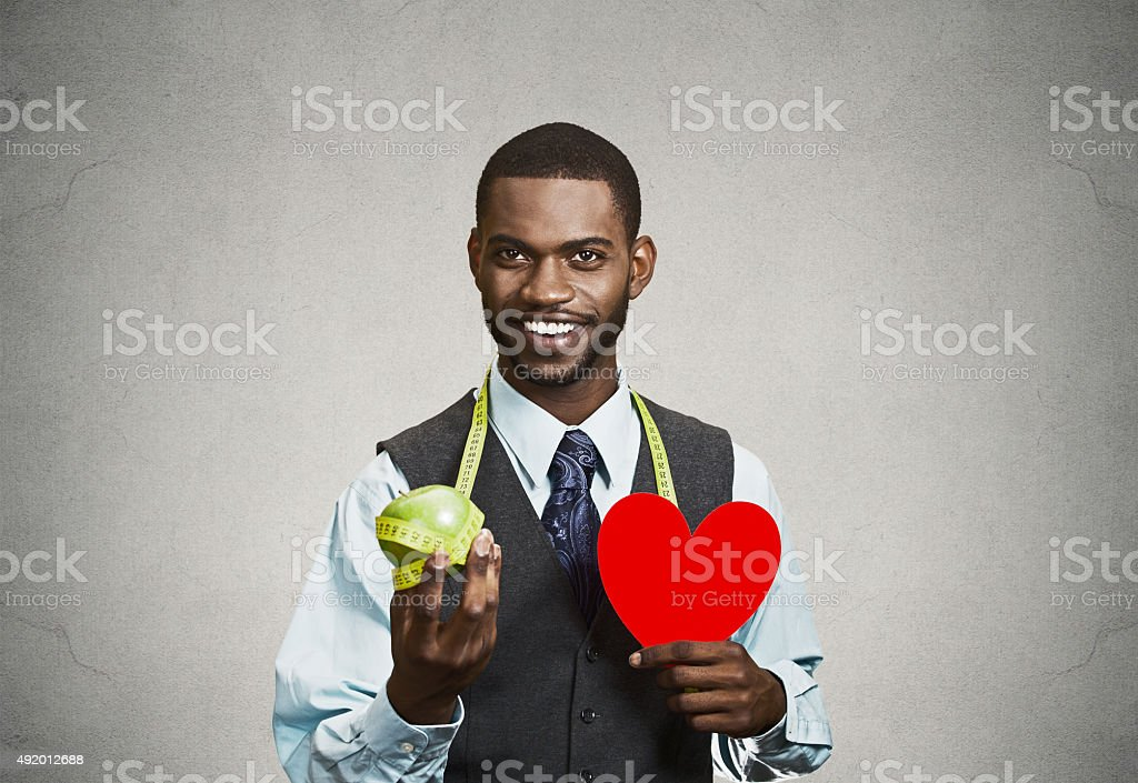 Man with red heart and green apple stock photo