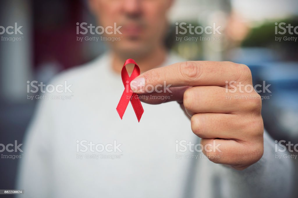man with red ribbon for the fight against AIDS stock photo