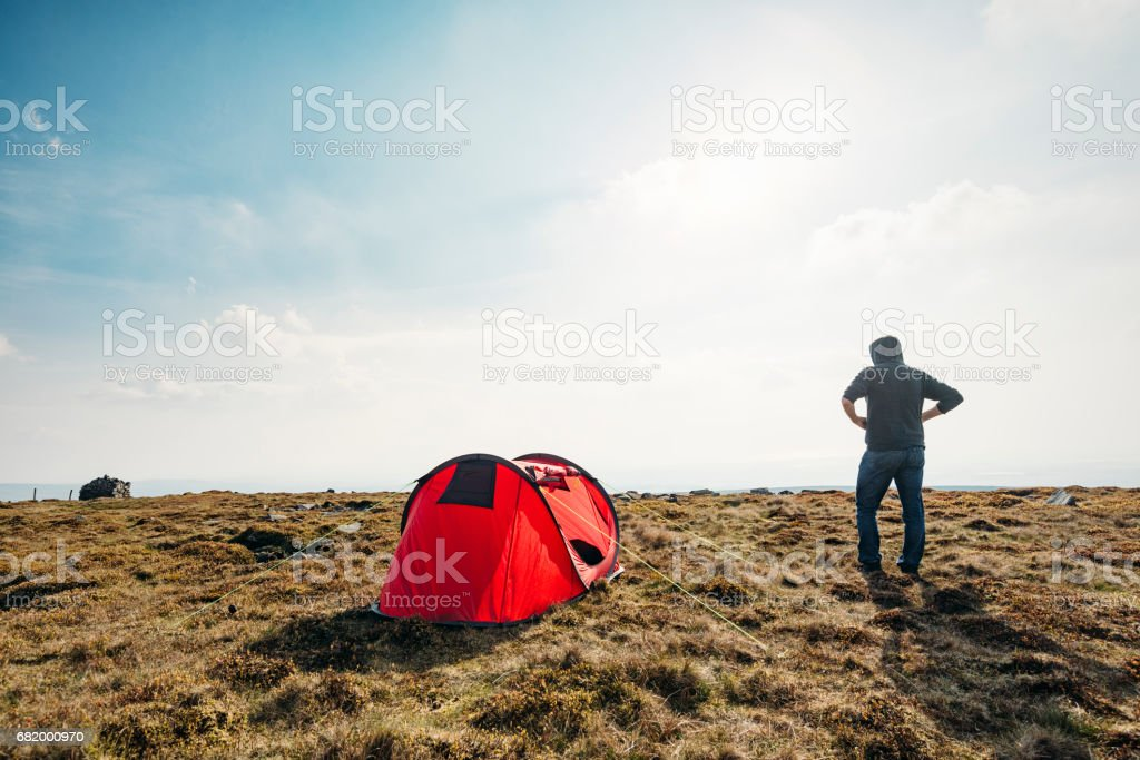 Man with red tent in remote location, backlit in sunshine. stock photo