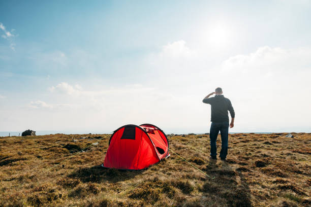 man with red tent in remote location, backlit in sunshine. - tent stock photos and pictures