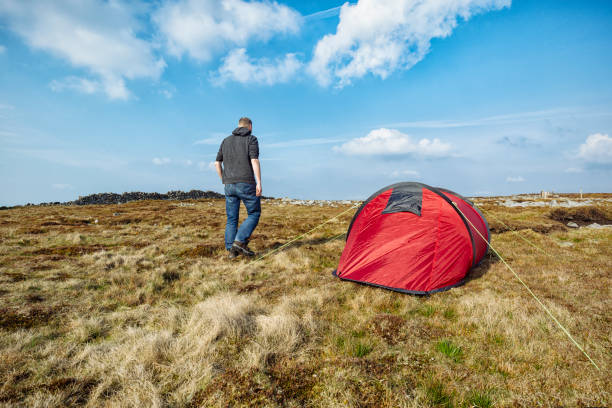 man with red tent in remote moorland setting, wild camping. - tent stock pictures, royalty-free photos & images