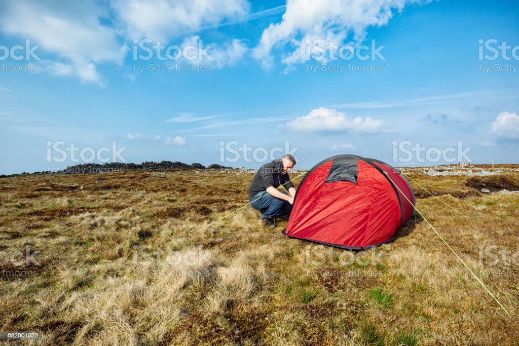 Man with red tent in remote moorland setting, Wild Camping. stock photo