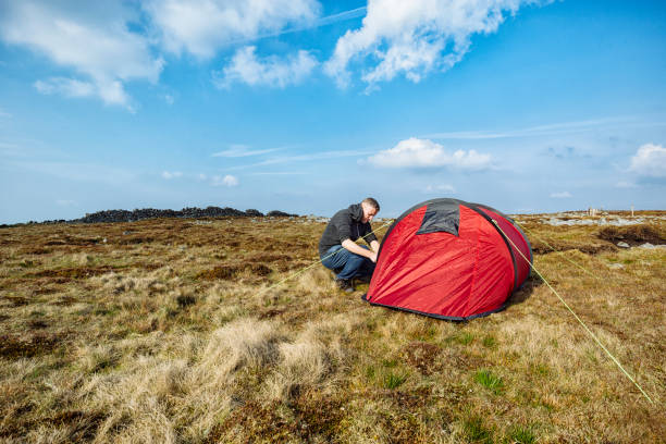 man with red tent in remote moorland setting, wild camping. - tent stock photos and pictures