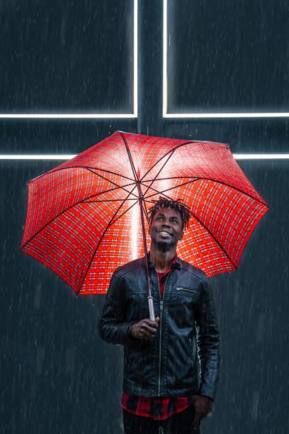mann mit rotem regenschirm unter regen - rote dreads stock-fotos und bilder