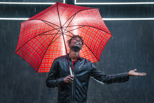 Man with red umbrella under rain